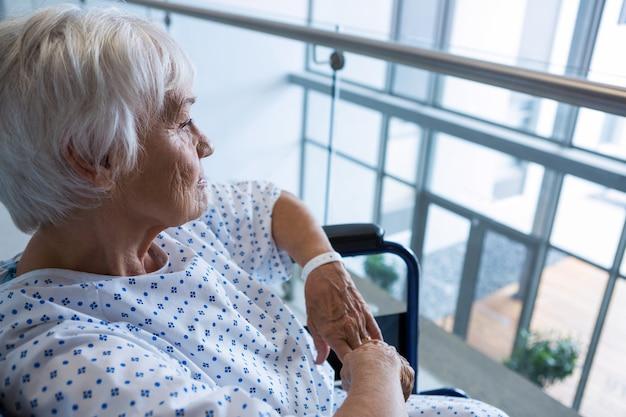Behinderter älterer patient im rollstuhl im krankenhausdurchgang im krankenhaus
