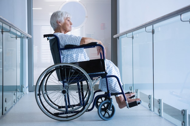 Behinderter älterer patient im rollstuhl im krankenhausdurchgang