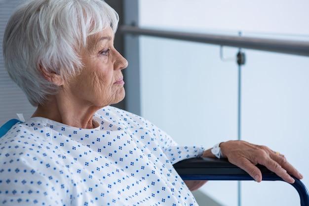 Behinderter älterer patient im rollstuhl im krankenhauskorridor