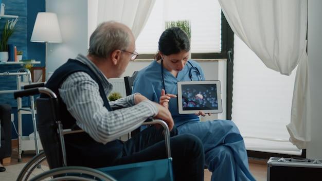 Behinderter alter mann, der sich die virusanimation auf dem tablet ansieht
