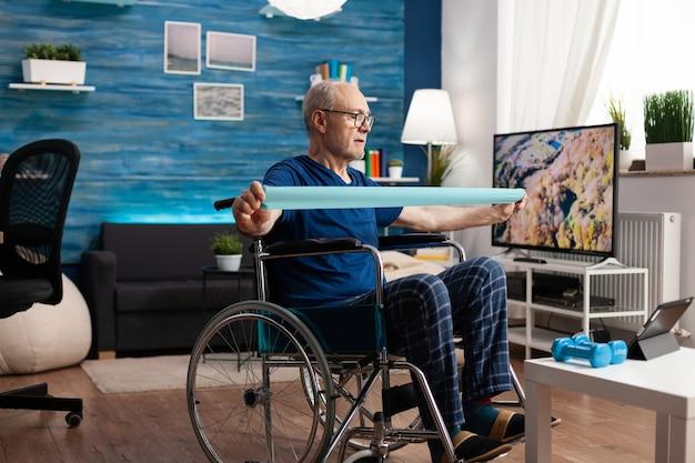Behinderter alter mann im rollstuhltraining armwiderstand trainiert körpermuskeln mit gummiband