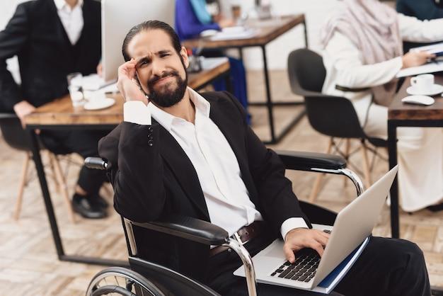 Behinderter arbeitnehmer mit laptop-kopfschmerzen im büro.