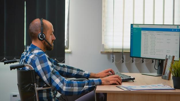 Behinderter behinderter operator, der im rollstuhl sitzt und telemarketing im geschäftsbüro macht. immobilisierter, behinderter, gelähmter freiberufler, der in einem finanzunternehmensgebäude mit heatset arbeitet