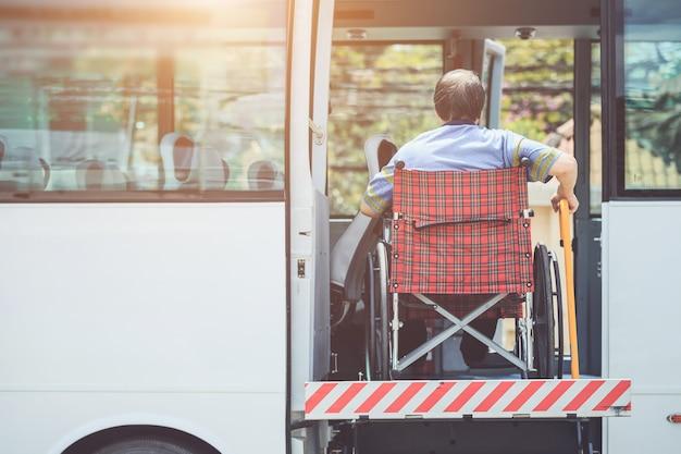 Behinderter, der auf rollstuhl sitzt und zum öffentlichen bus geht