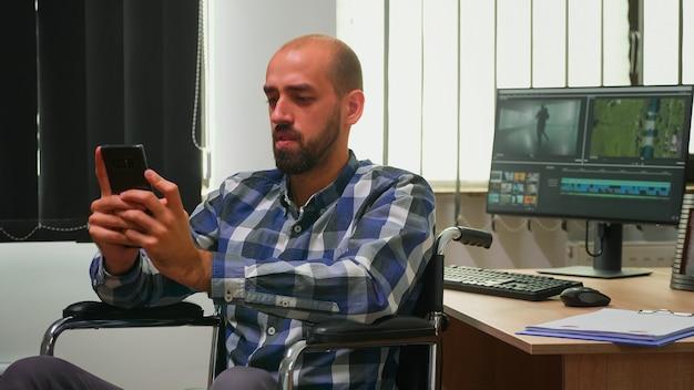 Behinderter fotodesigner, der im rollstuhl sitzt und im internet mit smartphone-sms, networking sucht. immobilisierter videofilmer, der ein neues projekt bearbeitet, das in einem modernen unternehmen arbeitet, das inhalte erstellt