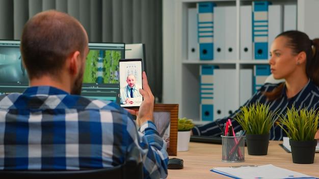 Behinderter freiberuflicher videograf, der während der arbeitszeit per videoanruf mit dem arzt spricht, während er inhalte im rollstuhl im modernen firmenbüro erstellt. creator-blogger, der vom fotostudio aus arbeitet.