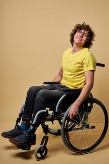 Behinderter fröhlicher behinderter mann, der räder berührt und im profil sitzt, während er isoliert im studio vorwärts bewegt, lächelt. isoliert auf beigem hintergrund