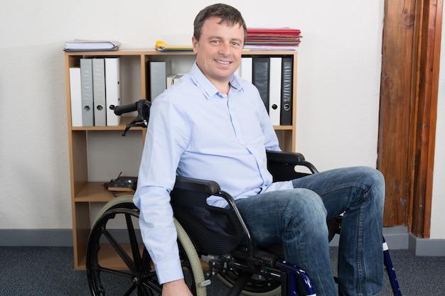 Behinderter geschäftsmann, der auf rollstuhl sitzt und computer im büro verwendet