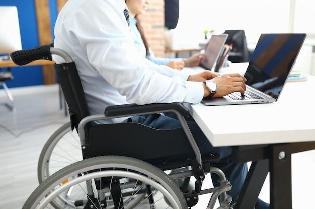 Behinderter geschäftsmann sitzt im büro im rollstuhl und arbeitet am laptop