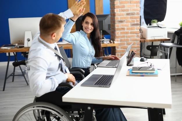 Behinderter geschäftsmann sitzt im rollstuhl am arbeitstisch im büro und grüßt geschäftsfrau