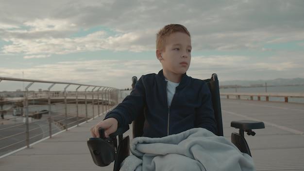 Behinderter junge auf dem weg an einem kühlen tag