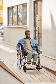 Behinderter junger afroamerikanischer mann, der einen manuellen rollstuhl benutzt, während er die rampe durch das haus herunterfährt?