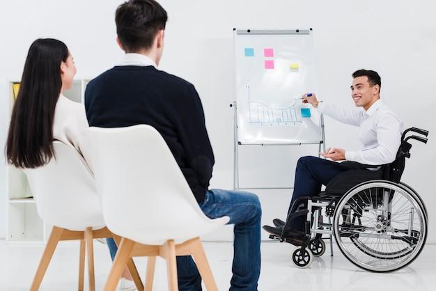 Behinderter junger geschäftsmann, der dem geschäftskollegen darstellung gibt