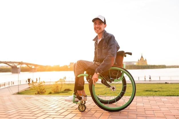 Behinderter junger mann im rollstuhl behinderter im rollstuhl für spaziergänge bei sonnenuntergang hochwertiges foto