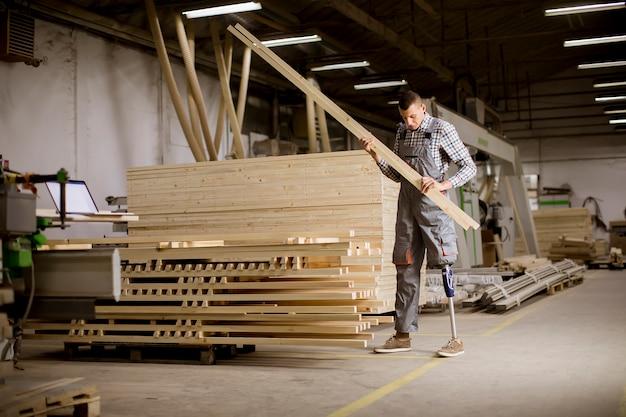Behinderter junger mann mit einem künstlichen bein arbeitet an der möbelfabrik