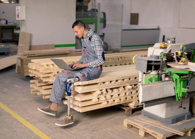 Behinderter junger mann mit einem künstlichen bein arbeitet in der möbelfabrik