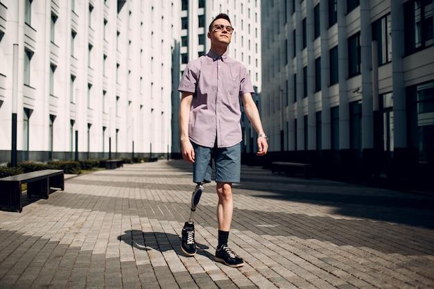 Behinderter junger mann mit fußprothese geht die straße entlang.