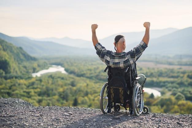 Behinderter kerl, der im rollstuhl mit den händen oben auf berg in umgebenen schönen landschaften sitzt