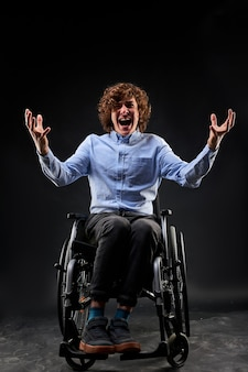 Behinderter kerl schreien vor verzweiflung, der auf rollstuhl sitzt, der auf schwarzer wand isoliert wird. porträt eines behinderten mannes, der die hände hebt und laut schreit