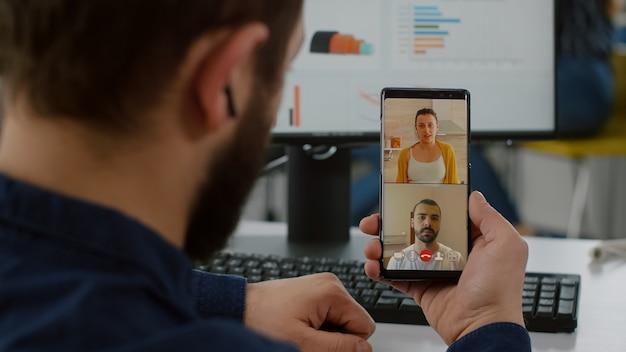 Behinderter manager, der per videoanruf mit freunden spricht, die während der arbeitszeit ein smartphone halten und eine pause machen
