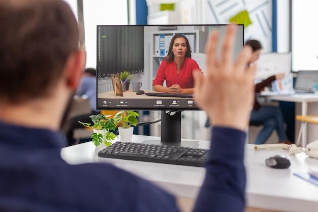 Behinderter manager spricht per videoanruf mit dem teamleiter, der während der virtuellen konferenz im strat-up-geschäftsbüro vor der kamera am computer sitzt