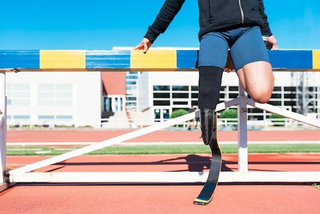 Behinderter mann athlet, der mit beinprothese streckt. paralympisches sportkonzept.