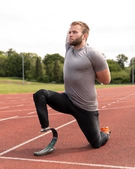 Behinderter mann auf der laufstrecke, der sich voller schuss streckt
