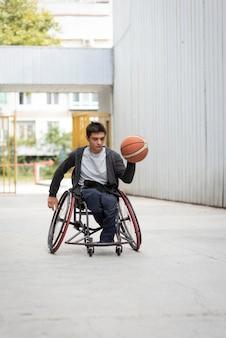 Behinderter mann, der basketball vollen schuss hält