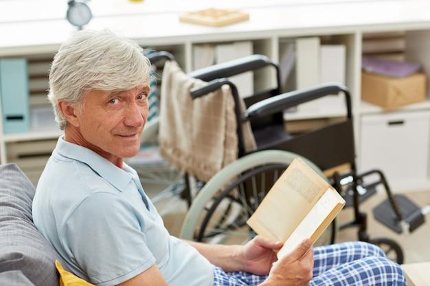 Behinderter mann, der ein buch liest