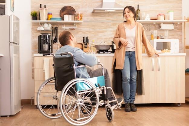 Behinderter mann, der im stuhl sitzt und mit seiner frau spricht, während er das essen zubereitet. behinderter, gelähmter, behinderter mann mit gehbehinderung, der sich nach einem unfall integriert.