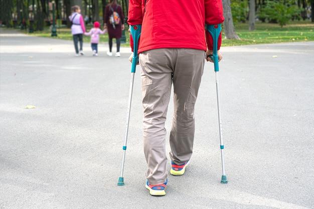 Behinderter mann, der krücken benutzt, um an der frischen luft zu gehen. erholung von einer beinverletzung.