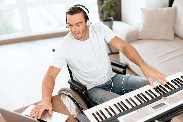 Behinderter mann, der lied mit synthesizer komponiert