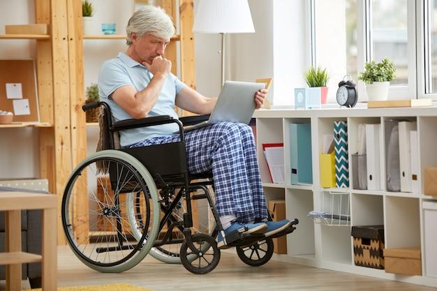 Behinderter mann, der online arbeitet