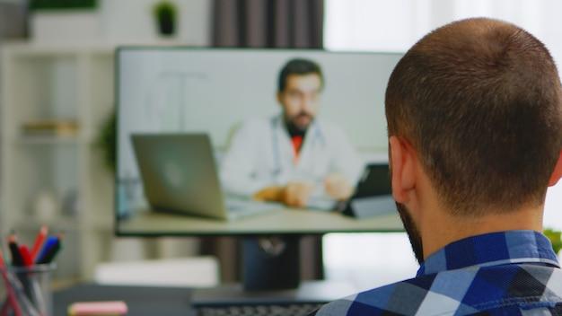 Behinderter mann, der während eines videoanrufs hilfe vom arzt sucht.