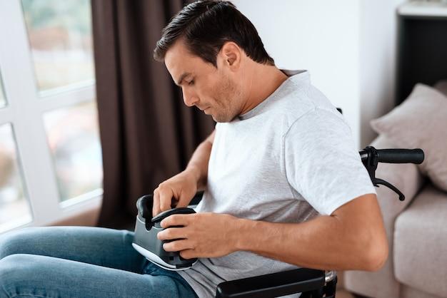 Behinderter mann im rollstuhl, der auf vr-schutzbrillen sich setzt.