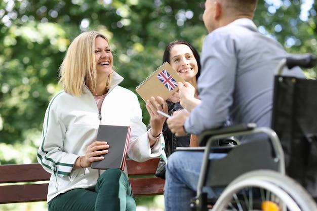 Behinderter mann im rollstuhl, der seinen freundinnen im ausländischen park englisches lehrbuch gibt