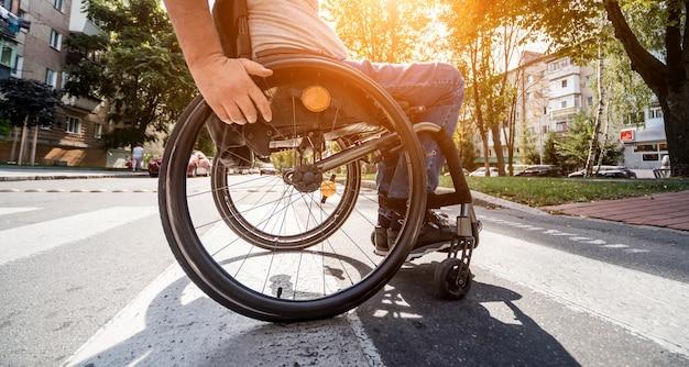 Behinderter mann im rollstuhl, der straßenstraße kreuzt