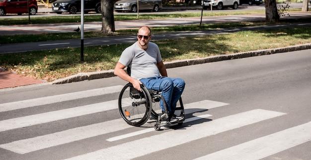 Behinderter mann im rollstuhl, der straßenstraße kreuzt.