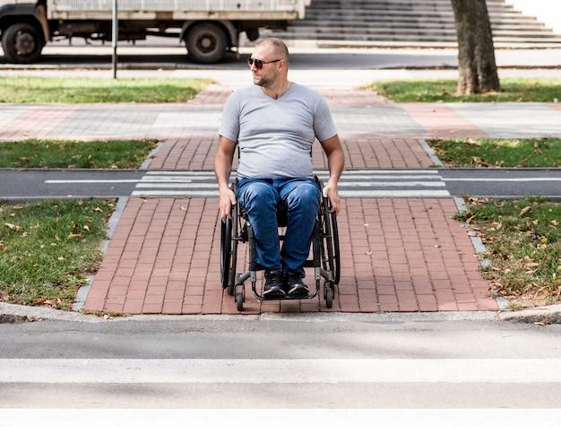 Behinderter mann im rollstuhl, der vorbereitet, die straße auf fußgängerüberweg zu überqueren