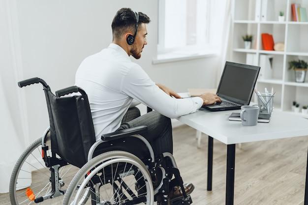 Behinderter mann im rollstuhl mit laptop-nahaufnahme