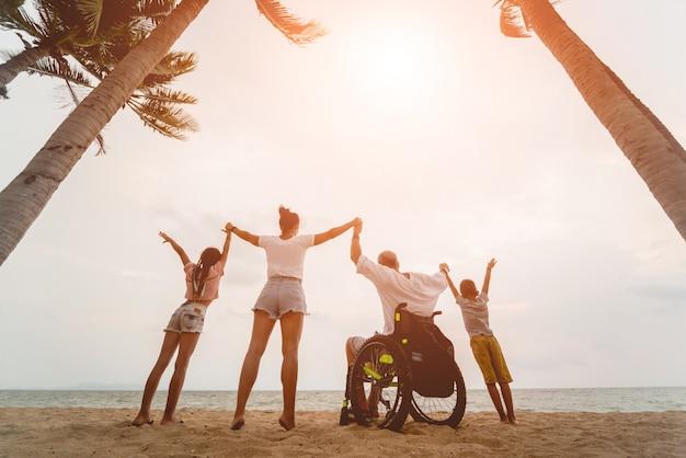 Behinderter mann im rollstuhl mit seiner familie am strand. silhouetten bei sonnenuntergang
