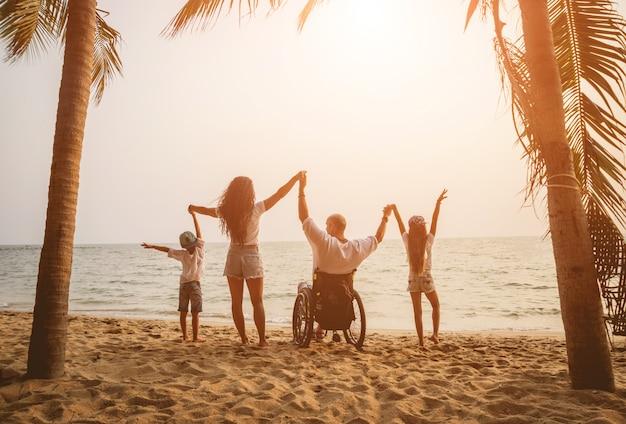 Behinderter mann im rollstuhl mit seiner familie am strand.