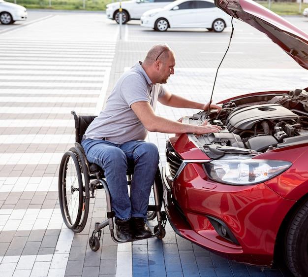 Behinderter mann im rollstuhl überprüft den motor seines autos auf dem parkplatz