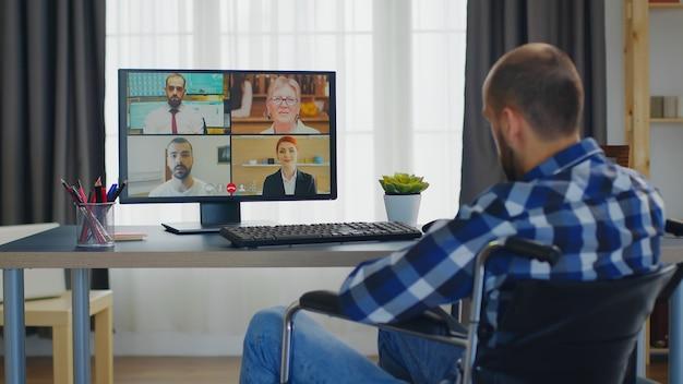 Behinderter mann im rollstuhl während einer videokonferenz mit arbeitskollegen.