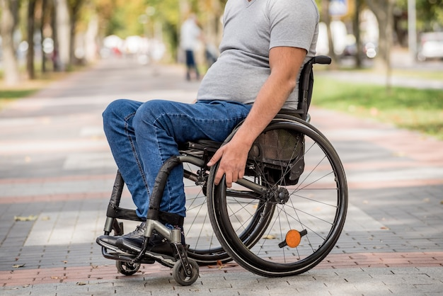 Behinderter mann im rollstuhlspaziergang an der parkgasse