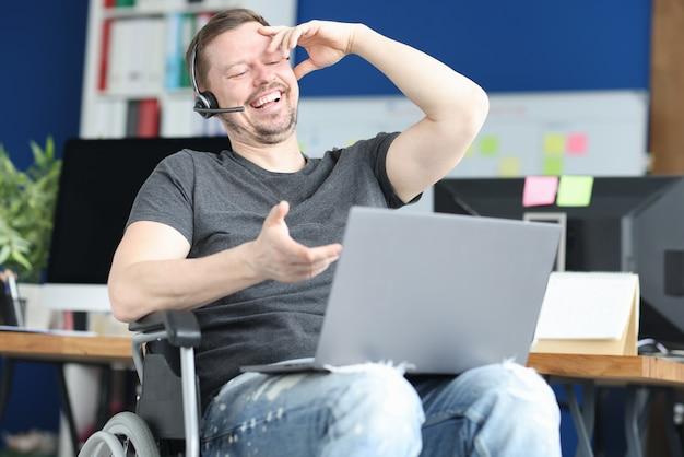Behinderter mann in kopfhörern, der über videoverbindung kommuniziert. konzept der beschäftigung von menschen mit behinderungen Premium Fotos