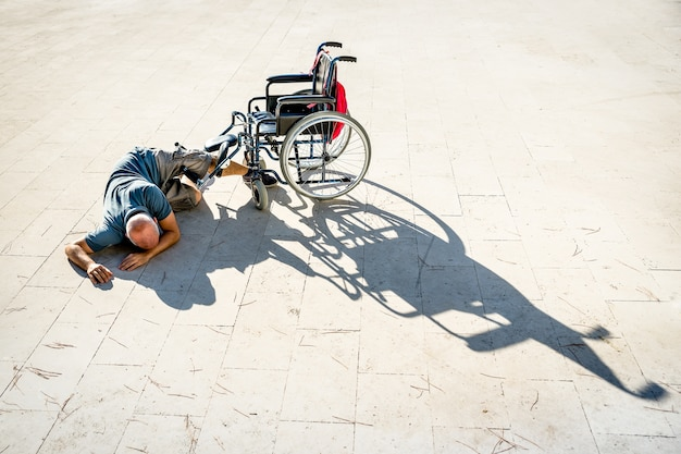 Behinderter mann mit behinderung, der einen unfall mit rollstuhlunfall hat