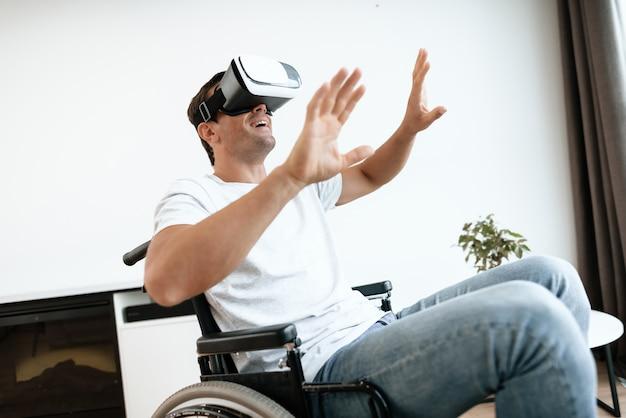 Behinderter mann mit den händen, die oben vr-schutzbrillen tragen.
