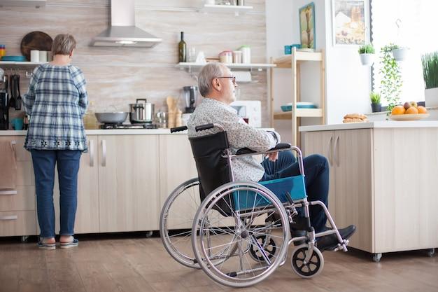 Behinderter mann sitzt im rollstuhl in der küche und schaut durch das fenster, während die frau das frühstück zubereitet. invalide, rentner, behinderte, lähmung.