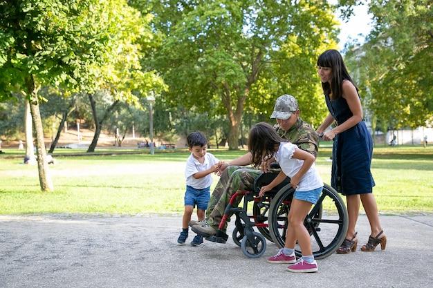 Behinderter militärvater im gespräch mit niedlichen kindern. kaukasischer vater mittleren alters in tarnuniform im freien mit familie. hübsche mutter, die rollstuhl schiebt. familientreffen und kriegsveteran konzept